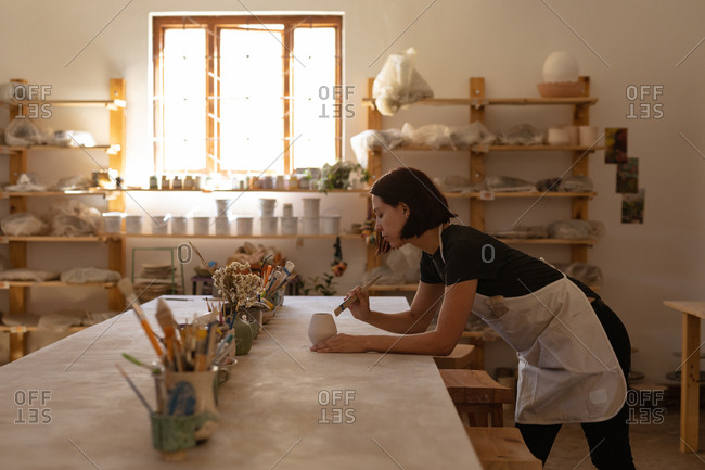 Side view of a young Caucasian female potter leaning on a work table and glazing a pot in a pottery studio