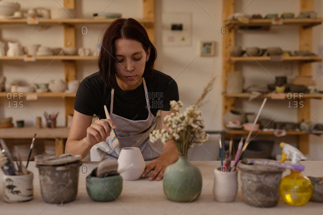 Front view close up of a young Caucasian female potter leaning over a work table and glazing a pot in a pottery studio, with pots and tools in the foreground