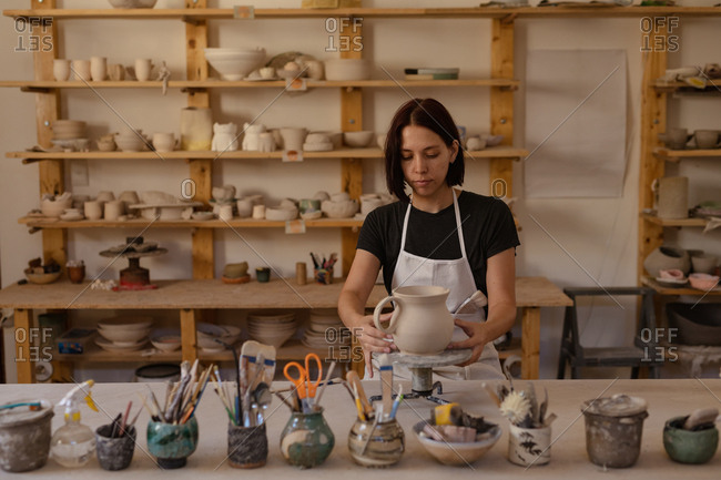 Front view of a young Caucasian female potter standing at a work table holding a jug on a banding wheel in a pottery studio, with pots and tools in the foreground