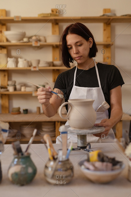 Front view close up of a young Caucasian female potter at a work table glazing a jug on a banding wheel in a pottery studio, with pots and tools in the foreground