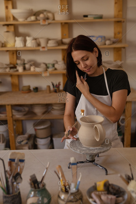 Front view a smiling young Caucasian female potter on the phone while glazing a jug in a pottery studio