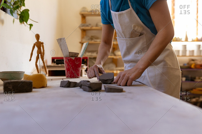 Side view mid section of a young Caucasian female potter wearing an apron working with pieces of clay at a work table in a pottery studio