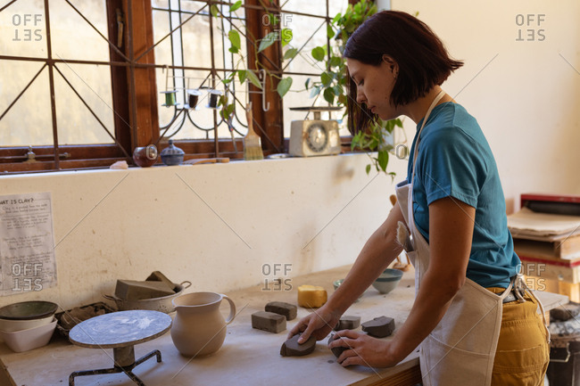 Side view of a young Caucasian female potter wearing an apron working with pieces of clay at a work table in front of a window in a pottery studio