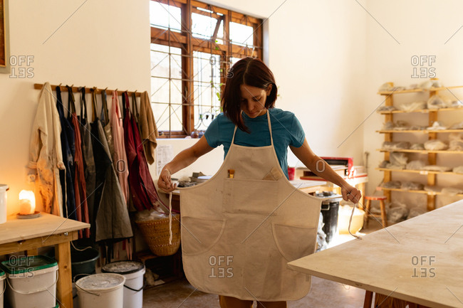 Front view of a young Caucasian female potter putting on an apron in preparation for work at a pottery studio