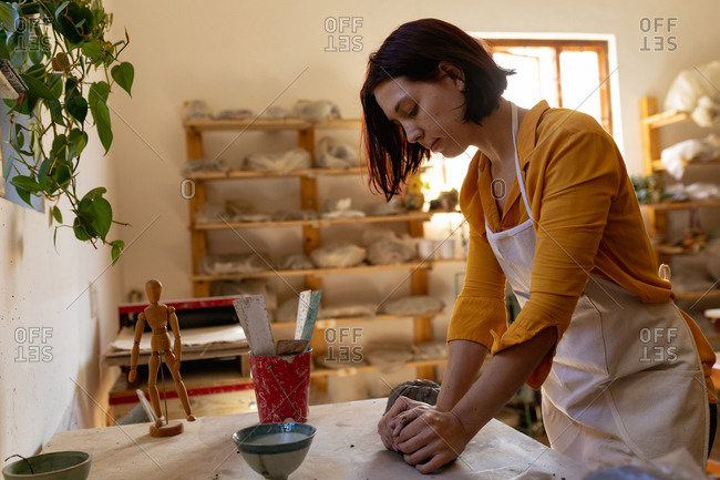 Side view of a young Caucasian female potter standing at a work table and kneading a piece of clay in a pottery studio