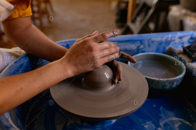 Close up of the hands of a young Caucasian female potter shaping wet clay on a potters wheel in a pottery studio