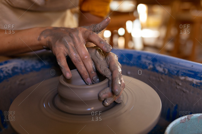 Close up of the hands of a young Caucasian female potter shaping wet clay into a pot on a potters wheel in a pottery studio