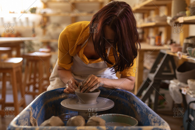 Front view of a young Caucasian female potter sitting at a potters wheel and shaping clay with her hands in a pottery studio