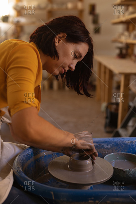 Side view close up of a young Caucasian female potter shaping wet clay into a pot on a potters wheel in a pottery studio