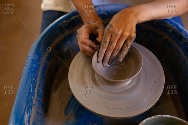Elevated close up of the hands of a young Caucasian female potter shaping wet clay into a bowl shape on a potters wheel in a pottery studio