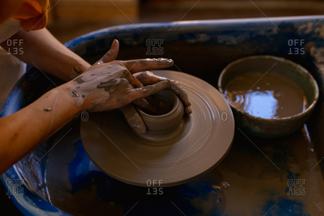 Elevated close up of the hands of a young Caucasian female potter shaping wet clay into a pot on a potters wheel in a pottery studio