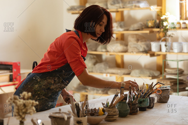 Side view of a young Caucasian female potter standing and selecting a tool from pots of tools on a work table in a pottery studio