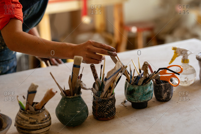 Close up of the hand of a young Caucasian female potter standing and selecting a tool from pots of tools on a work table in a pottery studio