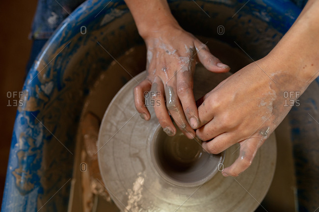 Elevated close up of the hands of a young Caucasian female potter shaping wet clay into a pot shape on a potters wheel in a pottery studio