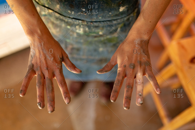 Elevated close up of the hands of a young Caucasian female potter with clay on them in a pottery studio