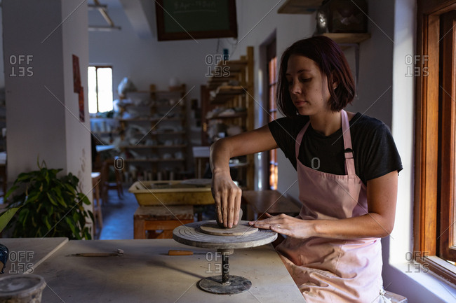 Side view of a young Caucasian female potter sitting at a work table working with clay on a banding wheel in a pottery studio