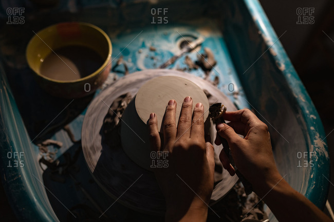 Elevated close up of the hands of a young Caucasian female potter using a tool to shape the base of a bowl on a potters wheel in a pottery studio