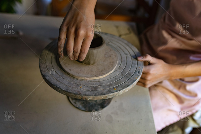 Elevated close up of the hands of a young Caucasian female potter shaping clay into a pot on a banding wheel in a pottery studio