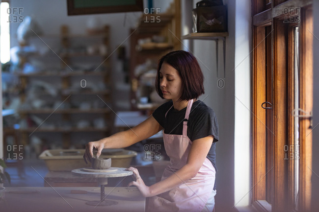 Side view of a young Caucasian female potter sitting at a work table in front of a window, working with clay on a banding wheel in a pottery studio