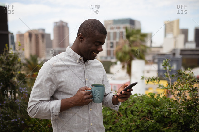 Side view close up of a young African American man standing outside on a balcony in the city holding a cup of coffee and looking down at his smartphone smiling