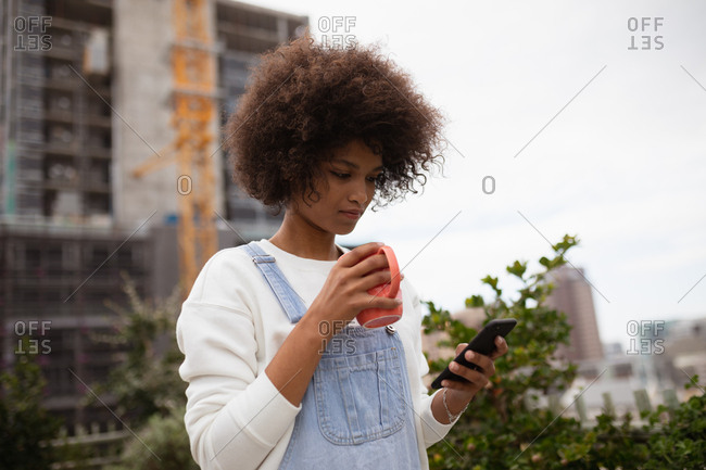 Side view close up of a young mixed race woman standing outside on a balcony in the city holding a cup of coffee and looking down at her smartphone
