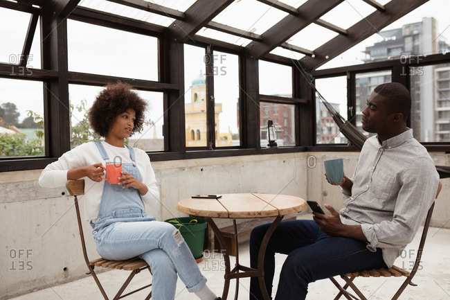 Side view of a young mixed race woman and a young African American man sitting at a table drinking coffee and talking in a glass roofed room on a rooftop, with city buildings in the background. The man is holding a smartphone
