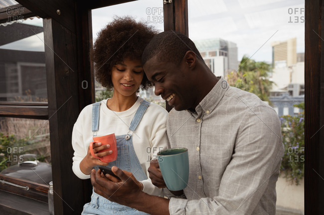 Front view close up of a young mixed race woman and a young African American man standing by a window drinking coffee and looking at his smartphone in a glass room on a rooftop, with city buildings in the background