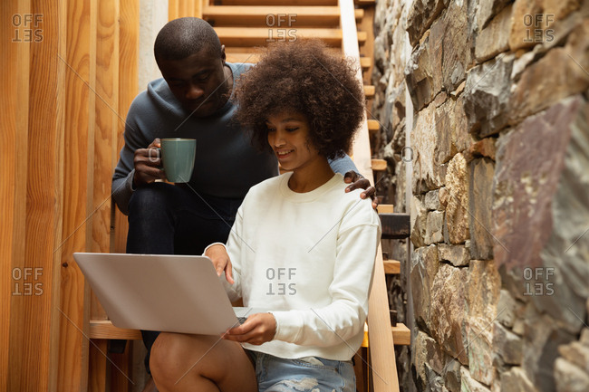 Front view close up of a young mixed race woman and a young African American man looking at a laptop computer and talking sitting on the stairs at home. The man is holding a cup of coffee and has his other hand on her shoulder