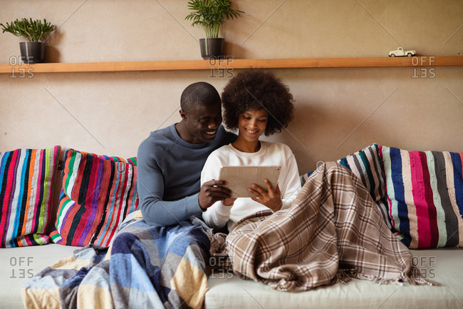 Front view close up of a young mixed race woman and a young African American man looking at a tablet computer and talking sitting together on a sofa at home. They are both holding the computer and have blankets over their legs