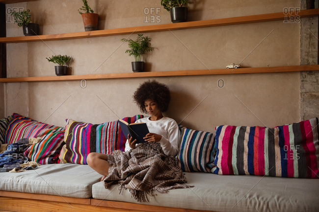 Front view of a young mixed race woman sitting on a sofa reading a book at home, leaning on cushions with a blanket over her legs