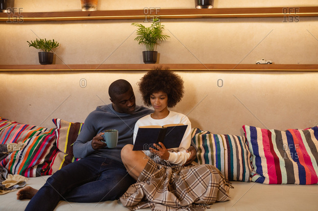 Front view of a young mixed race woman and a young African American man sitting on the sofa leaning on cushions looking at a book she is holding. The man is holding a cup of coffee and the woman has a blanket over her legs