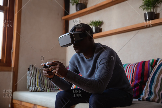 Side view close up of a young African American man wearing a VR headset and using a gamepad sitting on a sofa at home