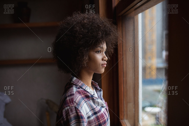 Side view close up of a young mixed race woman wearing a checked shirt standing by a window at home looking out