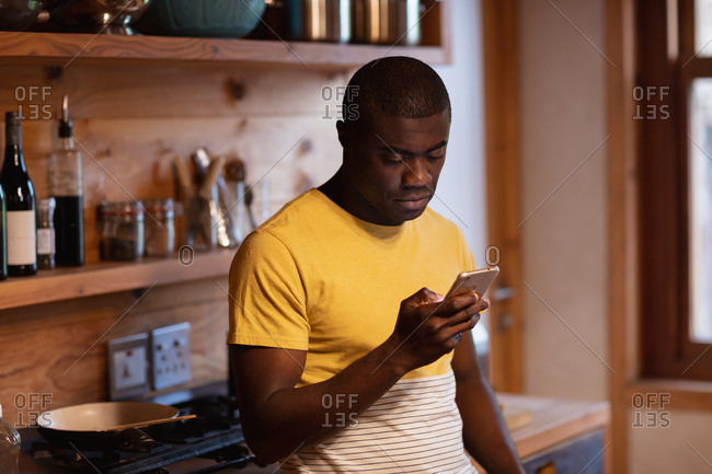 Side view close up of a young African American man wearing a yellow t shirt standing using a smartphone at home in his kitchen