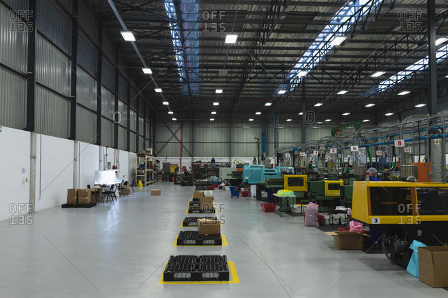 Front view of a row of processing equipment and an area for packing in a warehouse at a processing plant