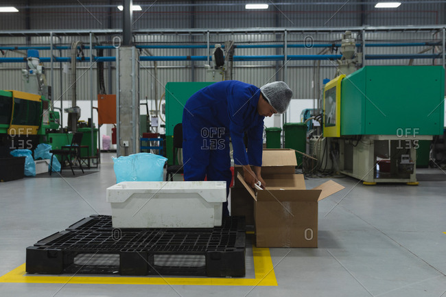 Side view close up of a young African American male factory worker packing products into boxes for shipping in a warehouse at a factory processing plant