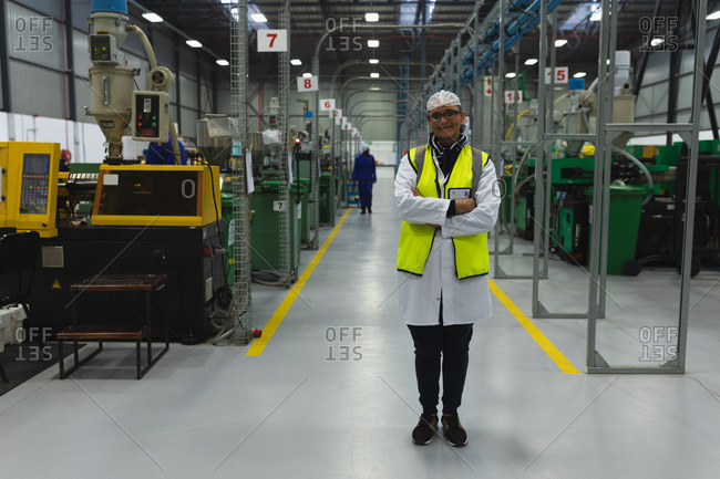 Portrait of a middle aged Caucasian woman wearing glasses and workwear standing between rows of equipment smiling in a warehouse at a processing plant, another worker visible in the background
