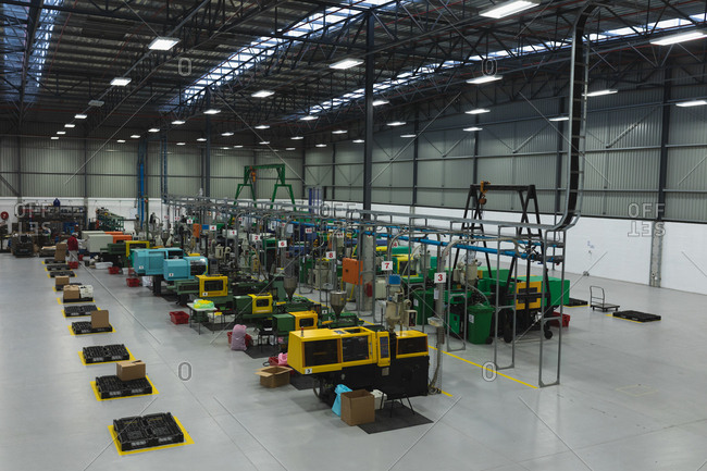 High angle view of a row of processing equipment and an area for packing in a warehouse at a processing plant