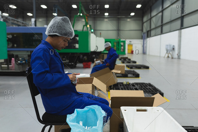 Side view close up of a young mixed race man sitting and packing product into boxes for shipping in a warehouse at a processing plant, a coworker visible in the background