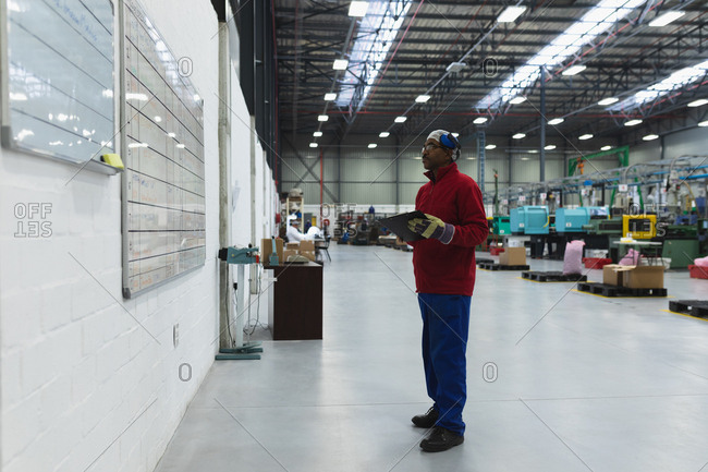 Side view of a middle aged African American male factory worker holding a clipboard checking information on a whiteboard in a warehouse at a processing plant