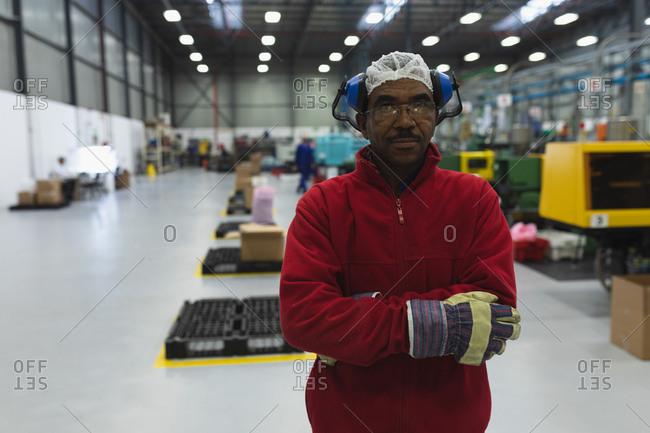 Portrait close up of a middle aged African American male factory worker dressed in workwear with ear defenders on his head, standing in a warehouse at a processing plant looking to camera with arms crossed