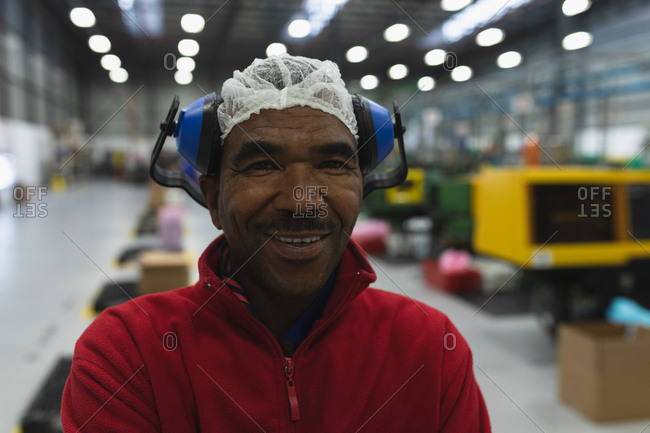 Portrait close up of a middle aged African American male factory worker dressed in workwear with ear defenders on his head, standing in a warehouse at a processing plant smiling to camera with arms crossed