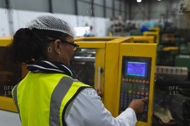 Rear view close up of a middle aged Caucasian female factory worker wearing glasses and workwear operating a machine at a processing plant