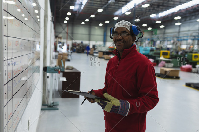 Side view close up of a middle aged African American male factory worker holding a clipboard checking information on a whiteboard turning to camera and smiling in a warehouse at a processing plant