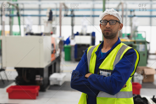 Portrait close up of a middle aged mixed race male factory worker wearing glasses and workwear looking to camera with arms crossed in a warehouse at a processing plant
