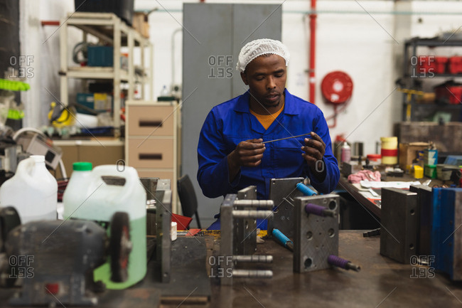 Front view close up of a young African American male factory worker sitting and inspecting equipment in the machine shop at a processing plant, with shelves of equipment in the background