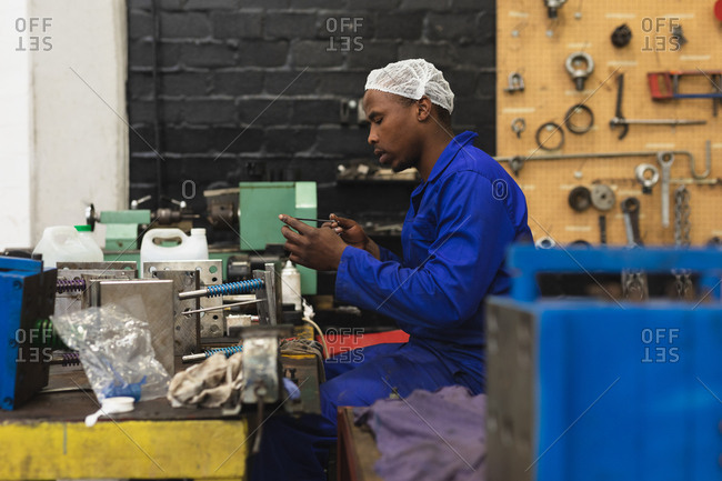 Side view close up of a young African American male factory worker sitting and inspecting equipment in the machine shop at a processing plant, with equipment and tools in the background