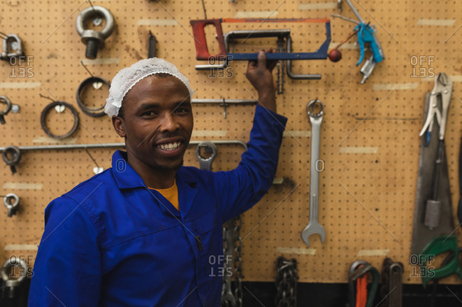 Portrait close up of a young African American male factory worker smiling to camera and reaching for a tool in the machine shop at a processing plant