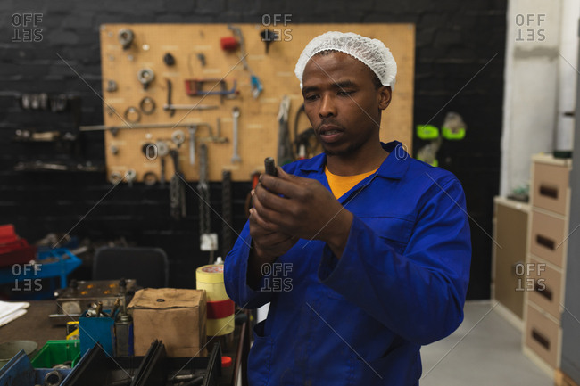 Front view close up of a young African American male factory worker inspecting equipment in the machine shop at a processing plant, with equipment and tools in the background