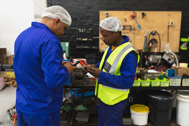 Side view close up of a middle aged mixed race male and a young African American male factory worker standing using smartphones in the machine shop at a processing plant, with equipment and tools in the background